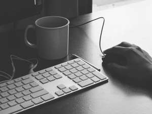 Hand resting on a mouse with keyboard and coffee nearby.